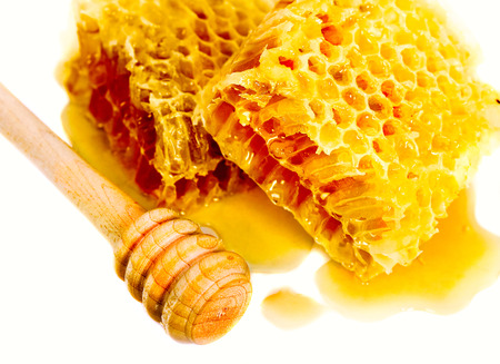 drizzler: sweet honeycomb and wooden drizzler, isolated on white