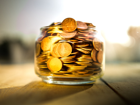 Coins in glass on the wooden background, financial concept
