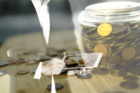 Double exposure of business man using tablet and golden coins in jar, technology and banking investment concept Stock Photo