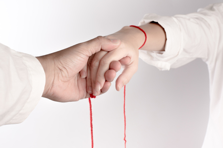 A hand of couple touch each other. The Faith of red thread brings destiny.