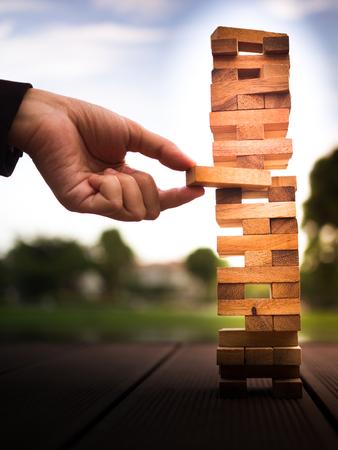 Hand des Geschäftsmannes herausziehen oder Holzblock auf dem Turm platzieren. Plan und Strategie im Geschäft. verwischen für den Hintergrund Standard-Bild