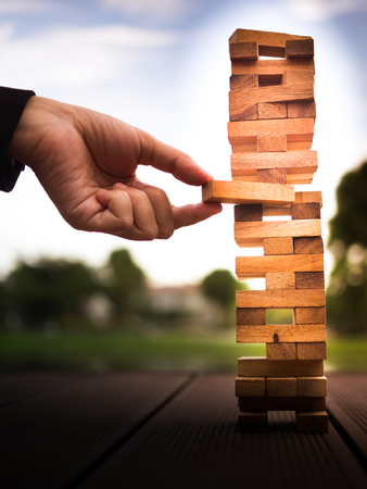 hand of businessman pulling out or placing wood block on the tower. plan and strategy in business. blur for background Banco de Imagens - 83348751