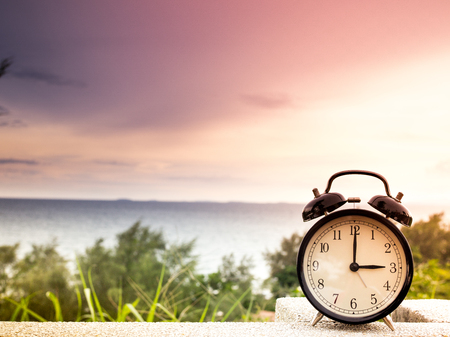 Close up an alarm clock with nature background, time concept Stok Fotoğraf