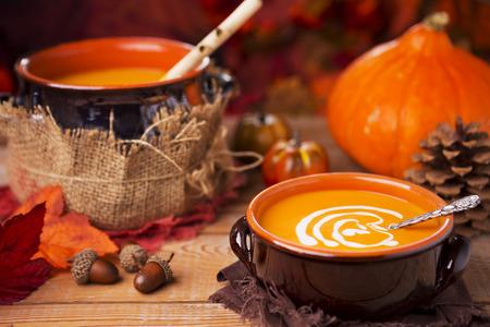 秋の装飾を持つ素朴なテーブルで自家製のクリーミーなカボチャのスープのボウル。