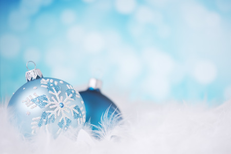Blue and silver Christmas baubles on a soft feathery surface in front of defocused blue and white lights.
