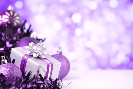 medium shot: Purple and silver Christmas baubles and a gift in front of defocused purple and white lights. Stock Photo