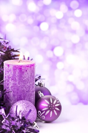 Purple and silver Christmas baubles and a candle in front of defocused purple and white lights. Foto de archivo