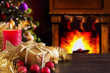 Christmas decorations, a gift and a candle in front of a fireplace. A fire is burning in the fireplace and Christmas stockings are hanging on the mantelpiece. A Christmas tree is standing next to the fireplace in the background.