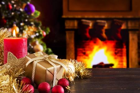 Kerstversiering, een geschenk en een kaars in de voorkant van een open haard. Een vuur brandt in de open haard en Kerstmis kousen zijn opknoping op de schoorsteenmantel. Een kerstboom staat naast de open haard in de achtergrond.