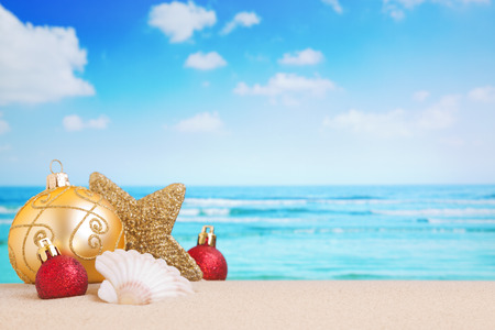 christmas baubles: Christmas decorations and baubles in the sand on a beach on a bright and sunny day. Stock Photo