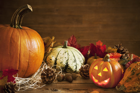 horizontal: A rustic autumn still life with pumpkins and a Jack OLantern on a wooden table. Stock Photo
