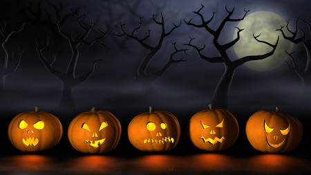 Frightening Halloween pumpkins or Jack OLanterns in a spooky and misty forest under a full moon at night. Stock Photo