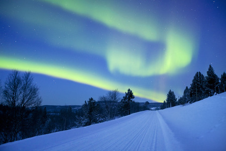Spectacular aurora borealis northern lights over a road through winter landscape in Finnish Lapland. Stock Photo