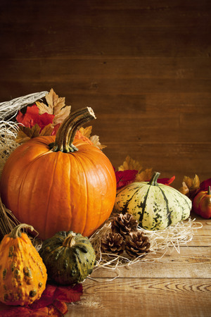fall background: A rustic autumn still life with pumpkins and a Jack OLantern on a wooden table. Stock Photo
