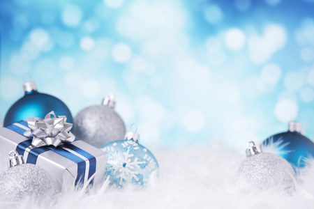 Blue and silver Christmas baubles and a gift on a soft feathery surface in front of defocused blue and white lights.