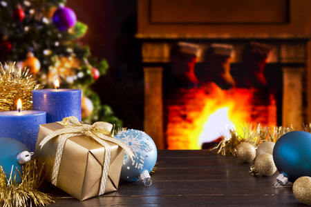 Christmas decorations, a gift and candles in front of a fireplace. A fire is burning in the fireplace and Christmas stockings are hanging on the mantelpiece. A Christmas tree is standing next to the fireplace in the background. Stock Photo