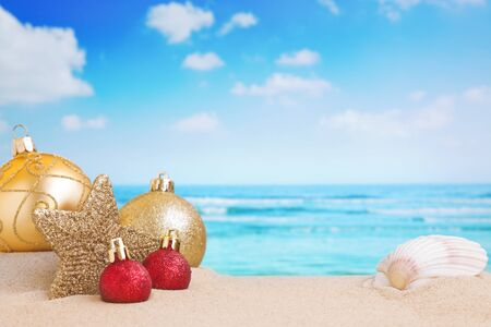 Christmas decorations and baubles in the sand on a beach on a bright and sunny day. Reklamní fotografie