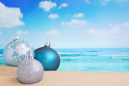christmas baubles: Christmas baubles in the sand on a beach on a bright and sunny day.