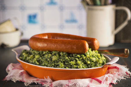 smoked sausage: A rustic kitchen with a dish with Boerenkool met worst or kale with smoked sausage, a traditional Dutch meal. With typical Dutch Delft blue tiles on the wall in the background.