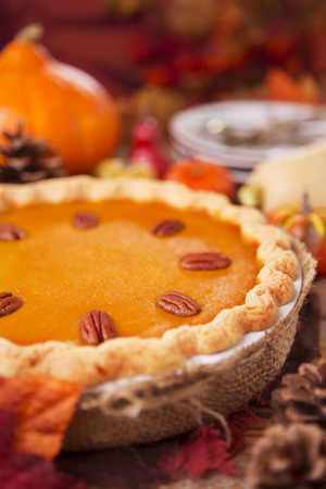 holiday food: Homemade pumpkin pie on a rustic table with autumn decorations. Stock Photo