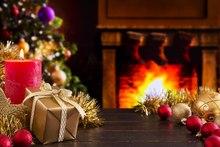 group of christmas baubles: Christmas decorations, a gift and a candle in front of a fireplace. A fire is burning in the fireplace and Christmas stockings are hanging on the mantelpiece. A Christmas tree is standing next to the fireplace in the background.