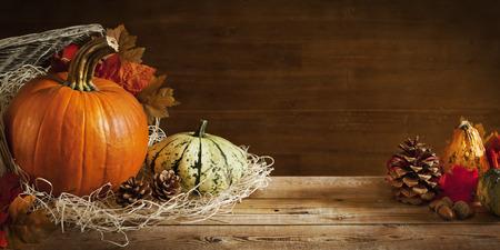 A l'automne rustique encore la vie avec des citrouilles et un panier sur une table en bois.