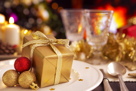 candle light table setting: A romantic Christmas dinner table setting with a gift and Christmas decorations. A fire is burning in the fireplace in the background. A Christmas tree is standing next to the fireplace.