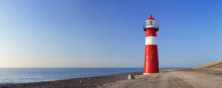 A red and white lighthouse at sea under a clear blue sky. Photographed near Westkapelle in Zeeland, The Netherlands. Stok Fotoğraf