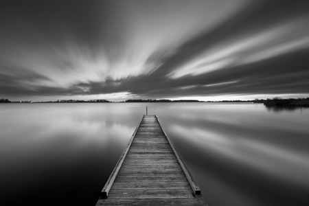 jetty: A small jetty on a lake near Amsterdam The Netherlands in black and white. A slow shutter speed was used to see the movement of the clouds in the sky. Photographed at dawn.