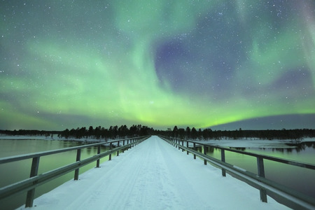 Spectacular aurora borealis northern lights over a bridge and a river in a snowy winter landscape in Finnish Lapland.