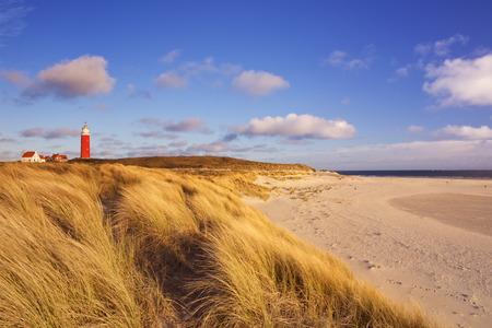De vuurtoren van het eiland Texel in Nederland omgeven door hoge zandduinen in prachtige vroege ochtend zonlicht. Stockfoto