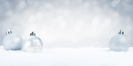 copy christmas: Silver Christmas baubles on snow with defocused silver and white lights in the background. Shallow depth of field. Stock Photo