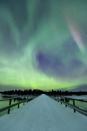 lapland: Spectacular aurora borealis northern lights over a bridge and a river in a snowy winter landscape in Finnish Lapland.