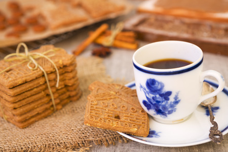 A cup of coffee with traditional Dutch speculaas (spiced shortcrust cookies). Authentic wooden cookie cutters especially made for these cookies can be seen in the background.
