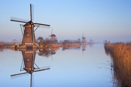 dutch culture: Traditional Dutch windmills reflected in perfectly still water on a cold morning in winter, at the Kinderdijk in The Netherlands.