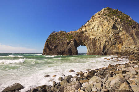 natural arch: The natural arch Senganmon  on the rocky coastline of the Izu Peninsula in Japan on a beautiful bright day. Stock Photo