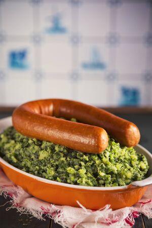 delftware: Una cucina rustica con un piatto con 'Boerenkool incontrato peggiore' o cavolo con salsiccia affumicata, un pasto tradizionale olandese. Con tipici olandesi Delft piastrelle blu sulla parete di fondo.