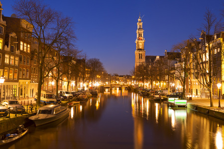 The Westerkerk Western Church along the Prinsengracht canal in Amsterdam at night.