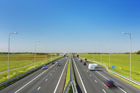 オランダで明るく晴れた日に芝生のフィールドを通過するトラフィックを高速道路。