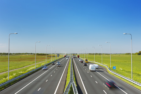 A highway with traffic through grassy fields on a bright and sunny day in The Netherlands. Stock Photo