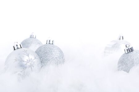 Silver Christmas baubles on a soft feathery surface with a white background.
