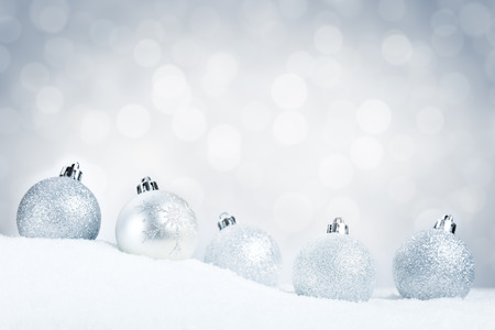 A row of silver Christmas baubles on snow with defocused silver and white lights in the background