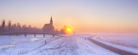 noord: A church in a frozen winter landscape in The Netherlands. Photographed at sunrise on a beautiful foggy morning.