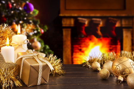 mantelpiece: Christmas decorations, a gift and candles in front of a fireplace. A fire is burning in the fireplace and Christmas stockings are hanging on the mantelpiece. A Christmas tree is standing next to the fireplace in the background. Stock Photo
