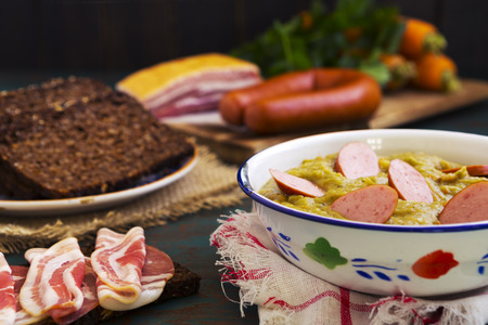 rustic kitchen: Hearty traditional Dutch pea soup with smoked sausage, rye bread and bacon. Or: erwtensoep met rookworst, roggebrood en spek.
