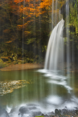 vertical image: The Nabegataki Falls on the island of Kyushu, Japan surrounded by autumn colours. Stock Photo