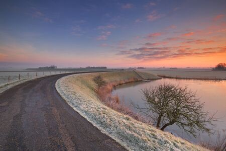 noord: Typical Dutch landscape on a frosty morning at sunrise. This is part of the West-Frisian Circular Dyke Stock Photo