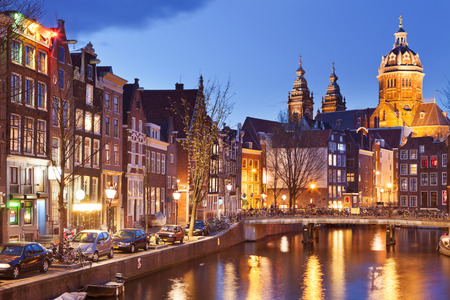 red light district: A canal in the red light district in Amsterdam, The Netherlands with the St. Nicholas church at the end. Photographed at night.
