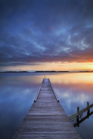 vertical image: A small jetty on a lake at sunrise. Photographed near Amsterdam in The Netherlands. Stock Photo