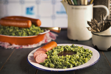 smoked sausage: A rustic kitchen with a plate with Boerenkool met worst or kale with smoked sausage, a traditional Dutch meal. Served with gravy. With typical Dutch Delft blue tiles on the wall in the background. Stock Photo